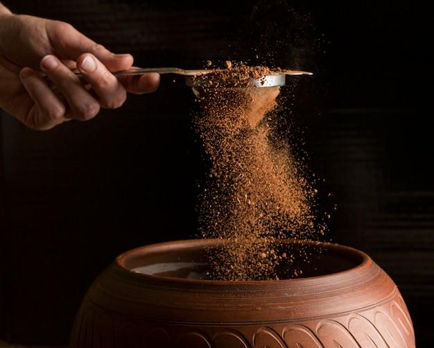Vue de face main tenant une passoire avec de la poudre de cacao