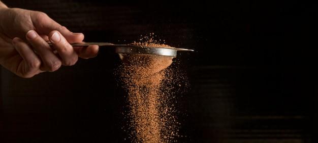Vue de face main tenant une passoire avec de la poudre de chocolat