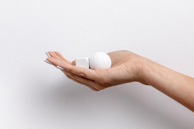 Vue de face de la main tenant un petit cube et une balle