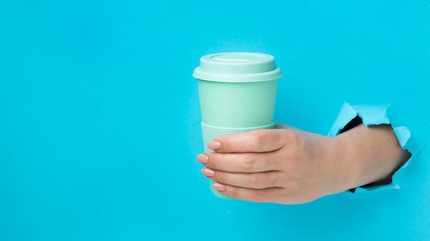 Vue de face main tenant une tasse réutilisable avec espace copie