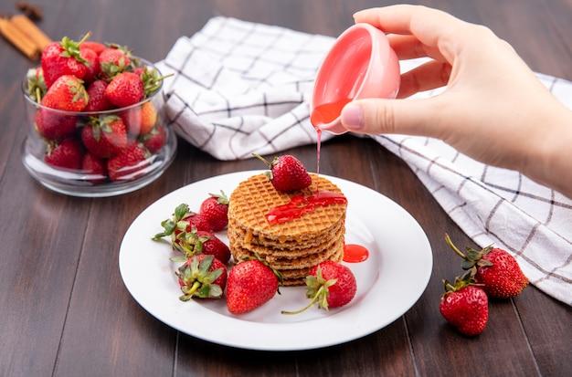 Vue de face de la main verser le sirop de fraise du bol sur les biscuits gaufres et bol de fraise sur la surface en bois