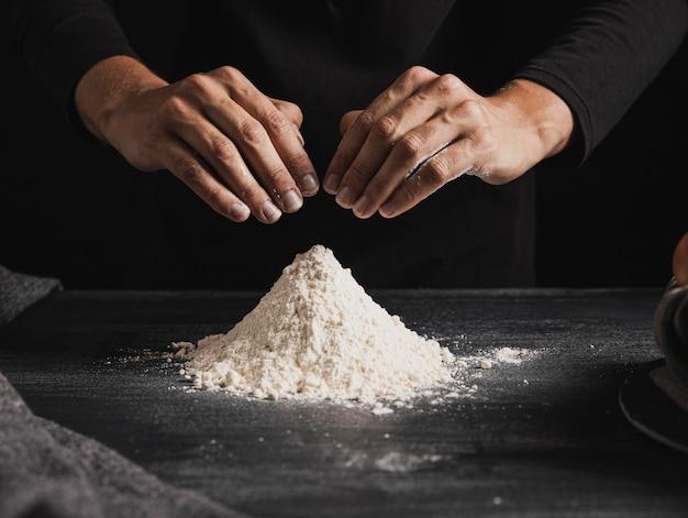 Vue de face des mains de boulanger mélangeant la farine