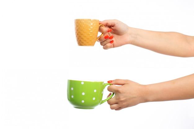 Une vue de face des mains féminines tenant différentes tasses colorées sur le blanc