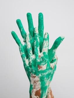Vue de face des mains peintes en vert