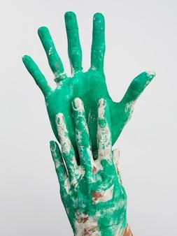 Vue de face des mains avec de la peinture verte