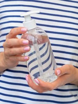 Vue de face des mains tenant une bouteille de désinfectant pour les mains