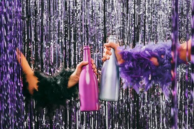 Vue de face mains tenant des bouteilles de champagne