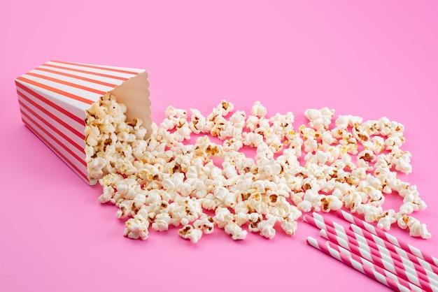 Une vue de face de maïs soufflé frais salé répartis sur rose, graine de maïs snack film