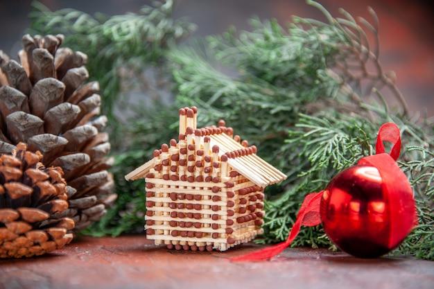 Vue de face maison d'allumettes boule d'arbre de noël branche de pin jouet avec pomme de pin photo du nouvel an