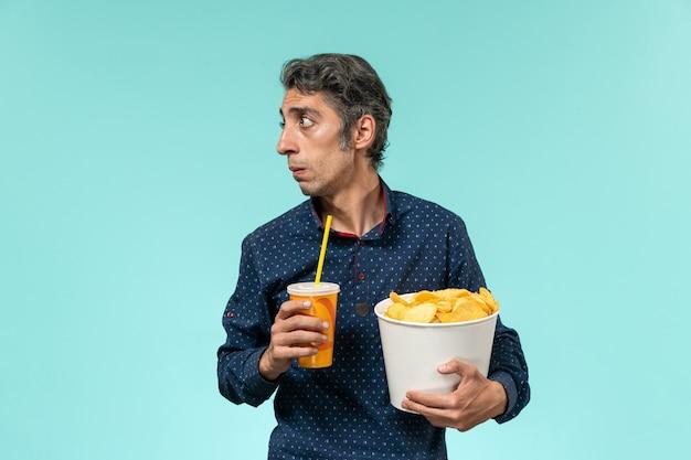 Vue de face mâle d'âge moyen tenant des cips de pommes de terre et boire sur une surface bleu clair