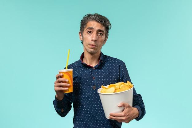 Vue de face mâle d'âge moyen tenant des cips de pommes de terre et boire sur une surface bleue
