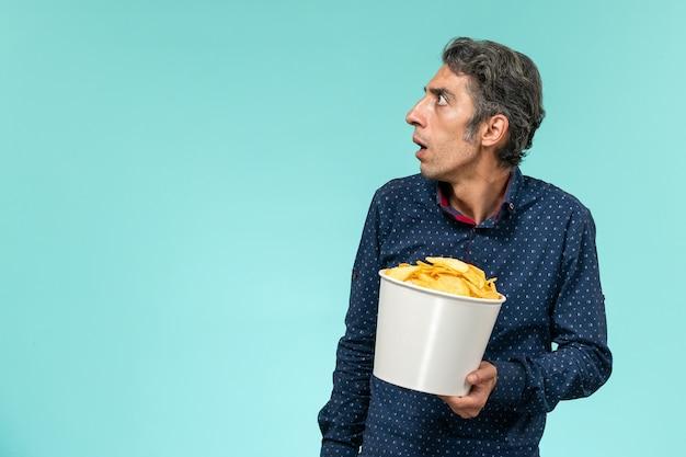Vue de face mâle d'âge moyen tenant des cips de pommes de terre sur le bureau bleu