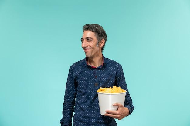 Vue de face mâle d'âge moyen tenant panier avec cips sur bureau bleu clair
