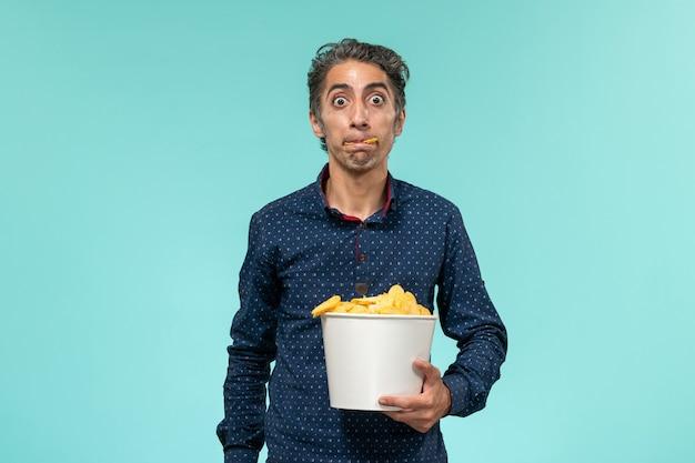 Vue de face mâle d'âge moyen tenant panier avec cips et manger sur une surface bleu clair