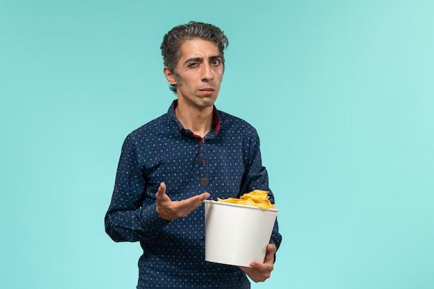 Vue de face mâle d'âge moyen tenant panier avec pommes de terre cips sur bureau bleu