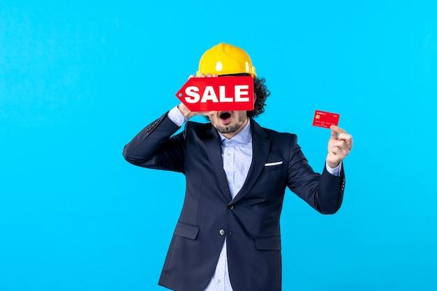 Vue de face mâle constructeur tenant une carte bancaire et vente écrit sur fond bleu conception maison travail architecture travail entreprise bâtiment