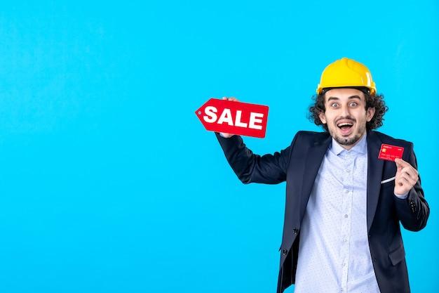 Vue de face mâle constructeur tenant une carte bancaire et vente écrit sur le fond bleu design maison architecture argent travail entreprise travaux de construction