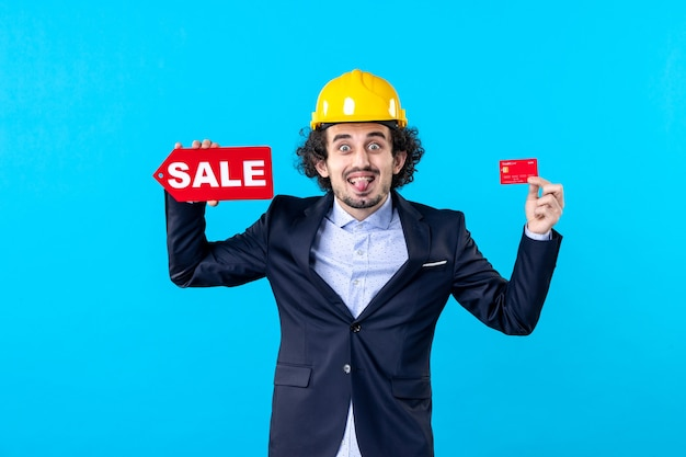 Vue de face mâle constructeur tenant une carte bancaire et vente écriture sur fond bleu conception maison travail architecture argent emploi entreprise
