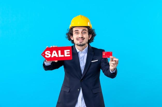 Vue de face mâle constructeur tenant une carte bancaire et vente écriture sur fond bleu conception maison travail architecture argent travail entreprise bâtiment