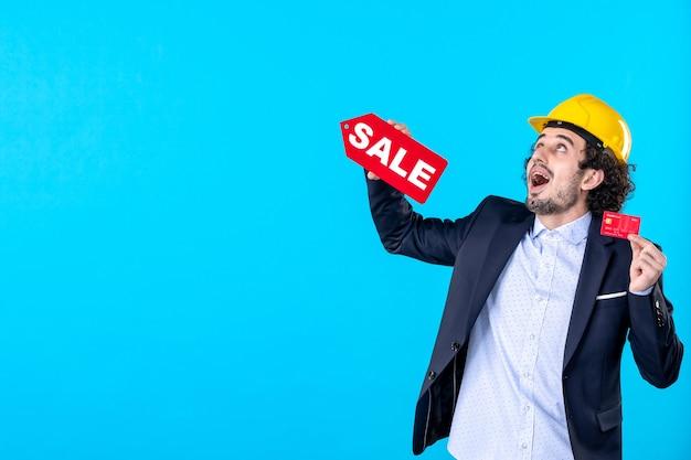 Vue de face mâle constructeur tenant une carte bancaire et vente écriture sur fond bleu design maison architecture argent emploi entreprise bâtiment travailleur