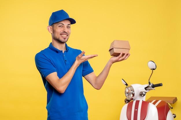 Vue de face male courrier holding petit paquet de nourriture sur les couleurs de travail jaune service travail de livraison uniforme travailleur vélo