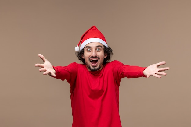 Vue de face mâle en rouge posant émotionnellement sur fond marron vacances émotion noël