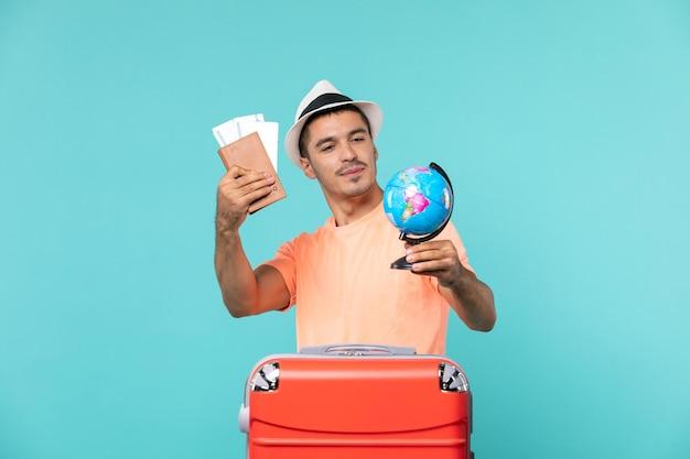 Vue de face mâle en vacances tenant un petit globe et des billets sur bleu clair