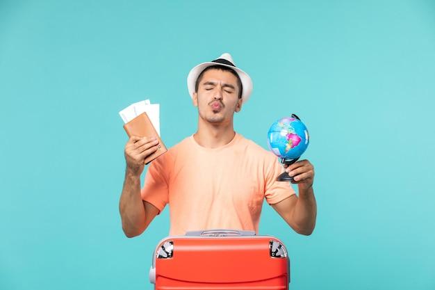 Vue de face mâle en vacances tenant un petit globe et des billets sur bleu