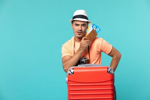 Vue de face mâle en vacances tenant ses billets sur bleu