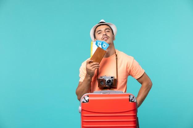 Vue de face mâle en vacances tenant ses billets sur le sol bleu voyage vacances voyage avion voyage