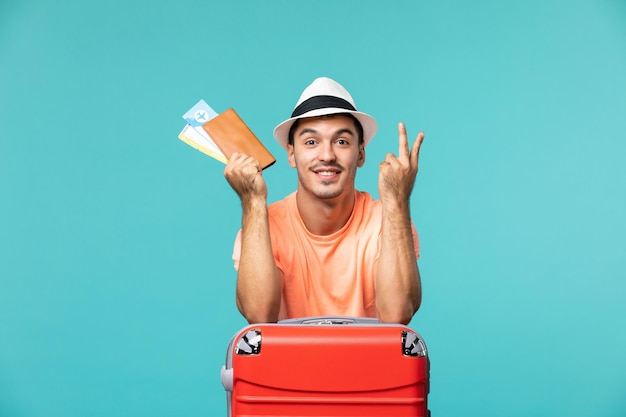 Vue de face mâle en vacances tenant ses billets souriant sur bleu