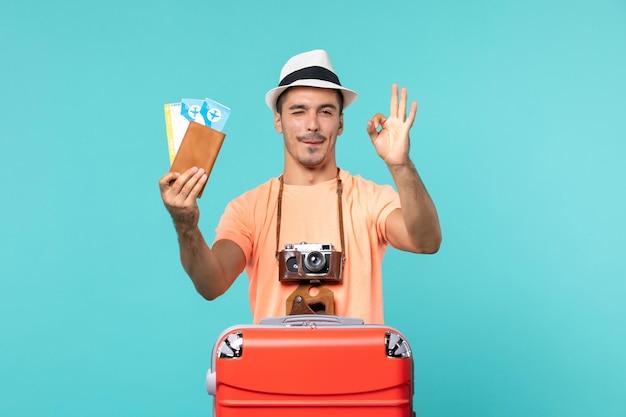 Vue de face mâle en vacances tenant ses billets avec sourire sur bleu