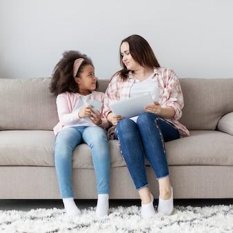 Vue de face maman et fille tenant des appareils électroniques