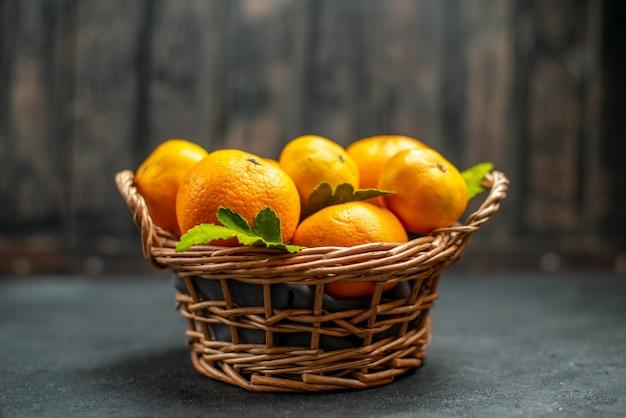 Vue de face des mandarines fraîches dans un panier en osier sur un endroit sombre et libre