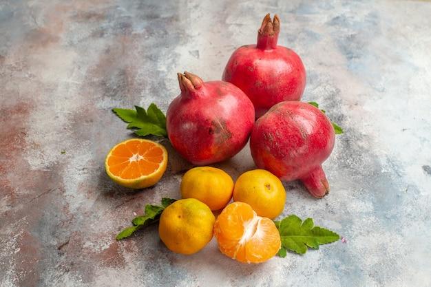 Vue de face mandarines fraîches avec grenades sur fond clair goût fruit couleur arbre vitamine