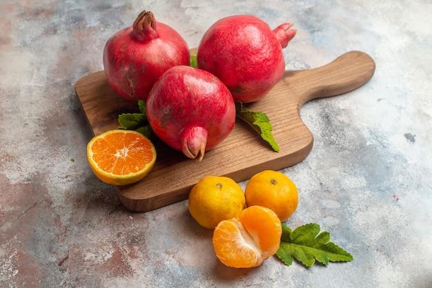 Vue de face mandarines fraîches avec grenades rouges sur fond clair jus couleur goût vitamine fruit arbre photo exotique