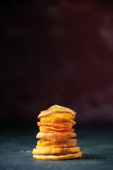 Vue de face de mandarines et de pommes en tranches de fruits sur fond sombre, jus de goût d'arbre fruitier de couleur mûre et moelleuse