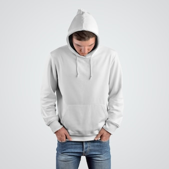 Vue de face d'une maquette de sweat à capuche blanc sur un jeune homme avec la tête inclinée. modèle de vêtements décontractés pour présentation dans le magasin.