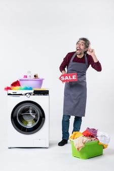 Vue de face mec gai en tablier brandissant une pancarte de vente debout près de la laveuse sur fond blanc