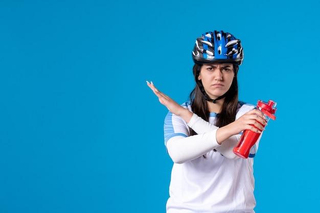 Vue de face mécontent de la jeune femme en vêtements de sport avec casque