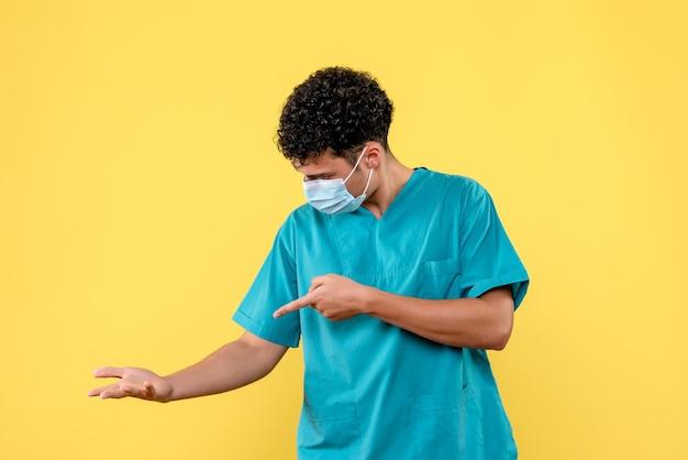 Vue de face médecin le médecin en masque parle de ce qu'il faut faire si votre main vous fait mal