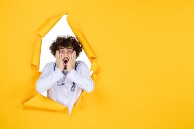 Vue de face médecin de sexe masculin en costume médical blanc sur un hôpital de couleur de virus de médecine de santé déchiré jaune
