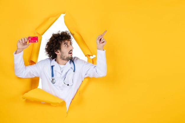 Vue de face médecin de sexe masculin en costume médical tenant une carte bancaire rouge sur la médecine de couleur jaune maladie hospitalière virus medic argent santé