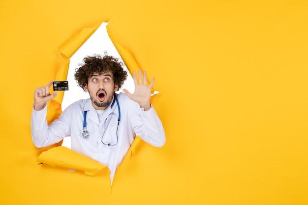 Vue de face médecin de sexe masculin en costume médical tenant une carte bancaire sur le virus de la santé de la maladie de l'hôpital de médecine de couleur jaune déchiré
