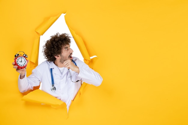 Vue de face médecin de sexe masculin en costume médical tenant des horloges sur des couleurs jaunes temps de médecine hospitalière santé médicale