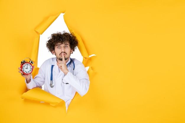 Vue de face médecin de sexe masculin en costume médical tenant des horloges sur l'hôpital jaune shopping couleur médecine temps medic