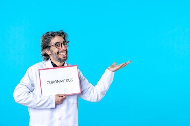 Vue de face médecin de sexe masculin tenant un coronavirus écrivant sur bleu