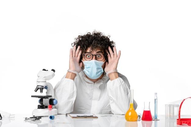 Vue de face médecin de sexe masculin en tenue de protection et masque juste assis avec des solutions sur blanc