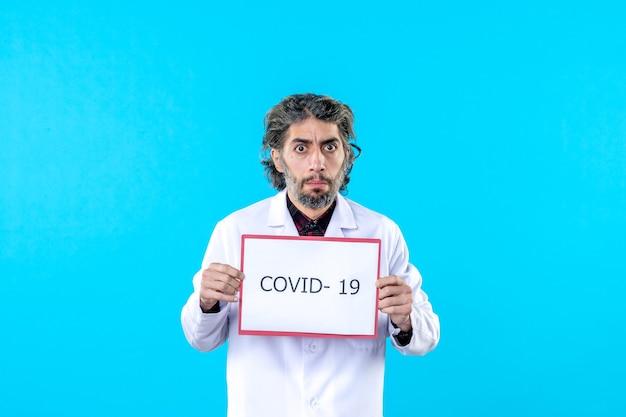 Vue de face médecin de sexe masculin en uniforme médical tenant covid- écrivant sur le bleu