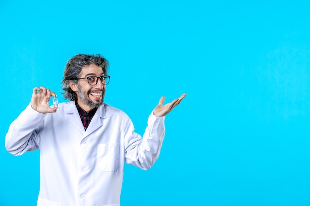 Vue de face médecin de sexe masculin en uniforme médical tenant une petite fiole sur le bleu